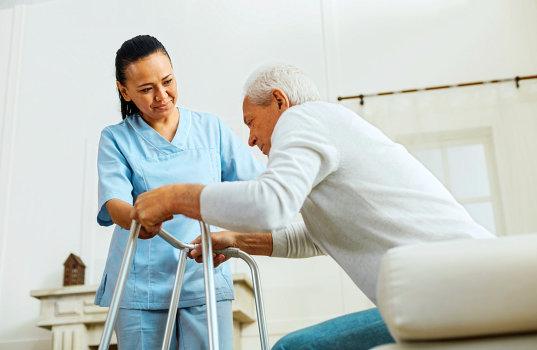 a caregiver woman helping an elderly man