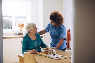 caregiver serving food to a senior woman