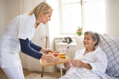 A young health visitor bringing breakfast to a sick senior women