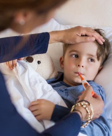 Nurse taking temperature on a kid