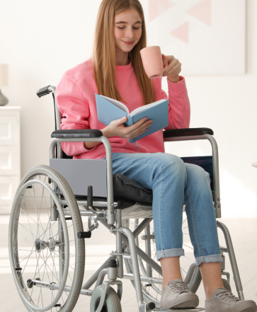 Lady sitting on wheelchair while reading and holding a mug
